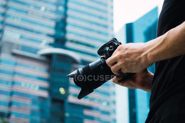 Gros plan des mains mâles tenant une caméra professionnelle en se tenant debout sur la rue — Photo de stock