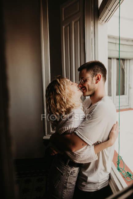 Glückliches Paar, das sich zu Hause umarmt und verbindet — Stockfoto