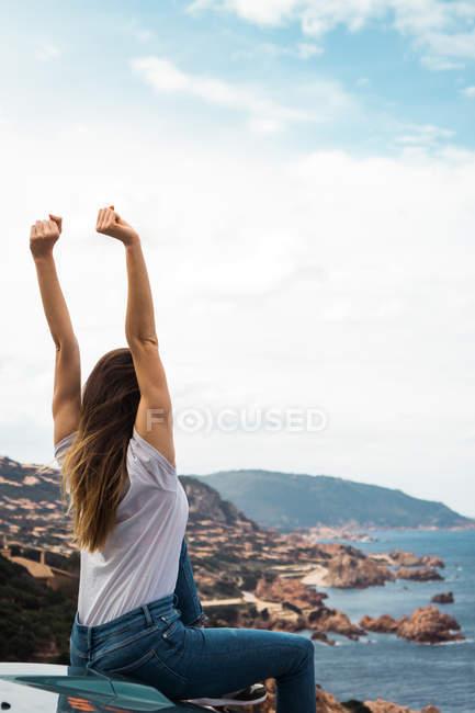 Mujer sentada en el maletero del coche a orillas del mar con los brazos arriba y mirando a la vista - foto de stock