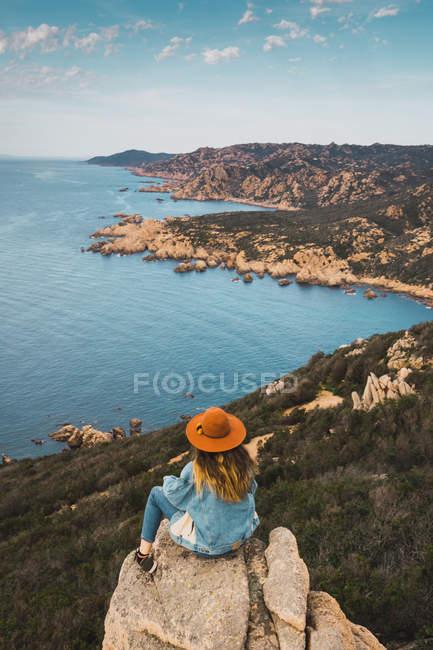 Donna sulla roccia al mare e guardando la vista — Foto stock