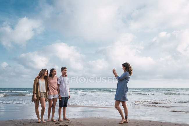 Woman photographing kids with smartphone on beach — Stock Photo