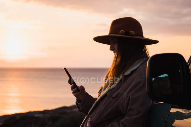 Жінка в капелюсі, за допомогою смартфона під час спершись на автомобіль на заході сонця — стокове фото
