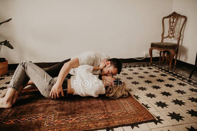 Heureux homme et femme gisant sur le sol et baiser à la maison — Photo de stock