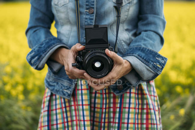 Woman in colored dress and denim jacket holding photo device in nature — Stock Photo