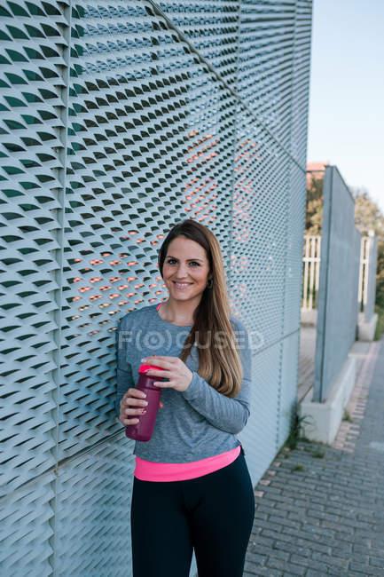 Retrato de jovem esportista mulher com uma garrafa de água — Fotografia de Stock