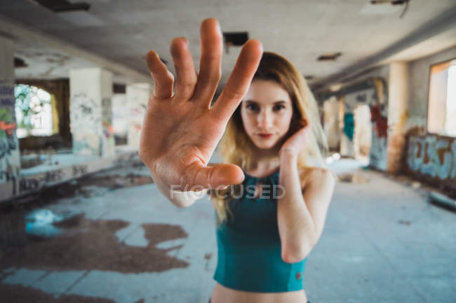 Skinny girl standing in decayed building with arm outstretched — Stock Photo