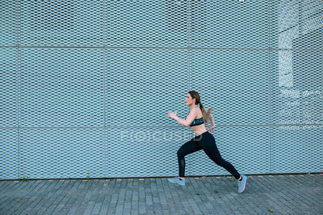 Young woman running outdoors in front of wall — Stock Photo