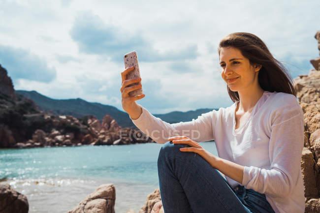 Жінка приймає selfie з смартфон на скелястому березі моря — стокове фото