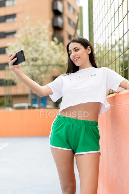 Young woman in sports clothes standing in city smiling and taking selfie with smartphone — Stock Photo