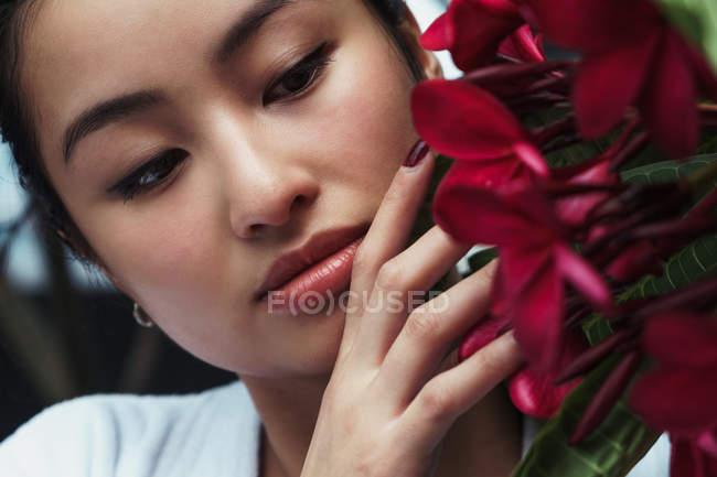 Bella giovane donna asiatica in piedi e toccare fiori rossi — Foto stock