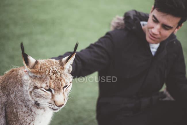 Junger Mann streichelt Luchs im Zoo — Stockfoto
