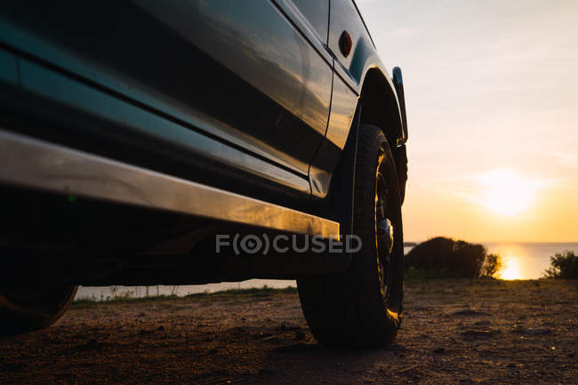 Close-up of Green car parked at seaside at sunset — Stock Photo
