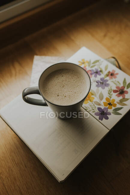 Cup of tasty warm drink placed on a book on table. — Stock Photo
