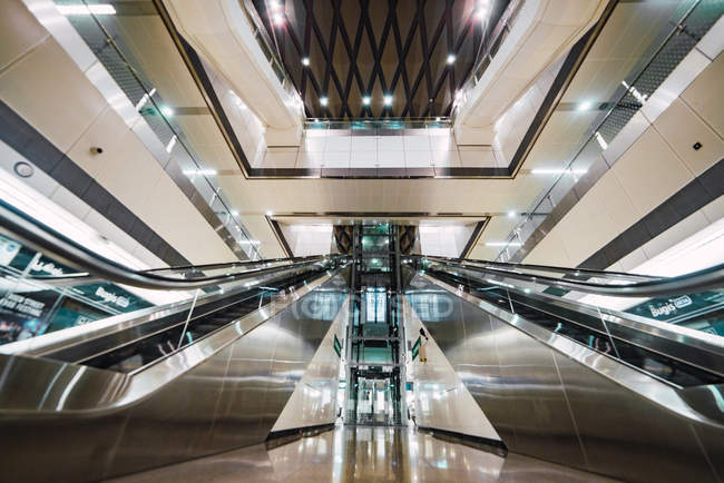 Два эскалатора, расположенных в ярко освещенном зале современного торгового центра, Сингапур — стоковое фото
