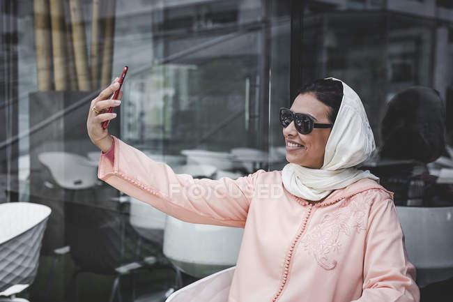 Marokkanerin mit Hijab und typische arabische Kleidung nehmen Selfie im café — Stockfoto