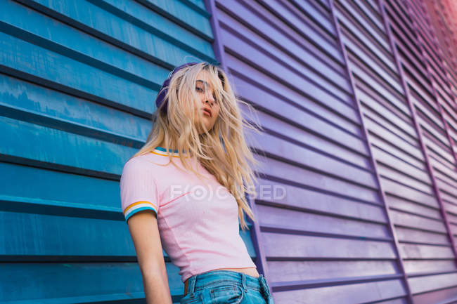 Young blond woman standing against bright multicolored wall and listening to music with purple headphones — Stock Photo