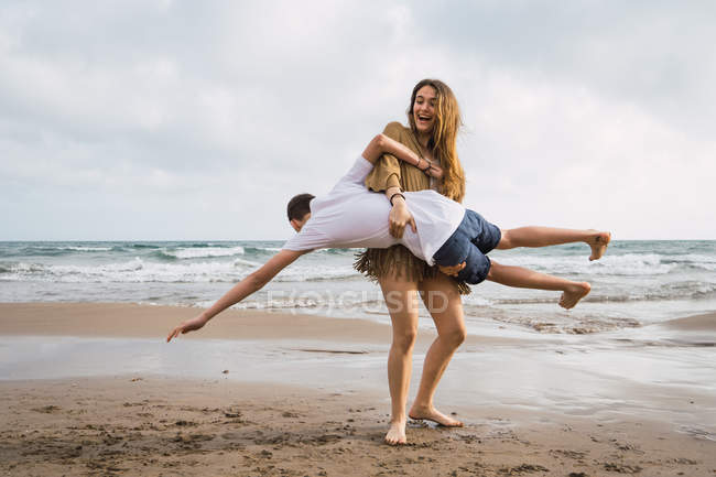 Two laughing teen friends fooling around on seashore in summer — Stock Photo
