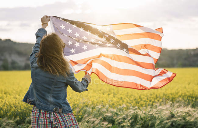 Woman in colored skirt holding american flag in field with yellow flowers on Independence Day — Stock Photo