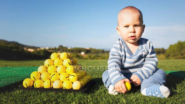 Adorable petit garçon assis sur une pelouse verte à pile de balles de golf jaune — Photo de stock