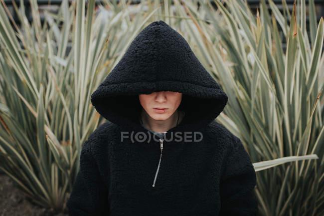 Man wearing black hooded jacket standing in green bush — Stock Photo