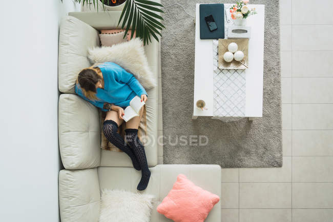 Woman in blue sweater sitting on couch in stylish living room and reading book — Stock Photo