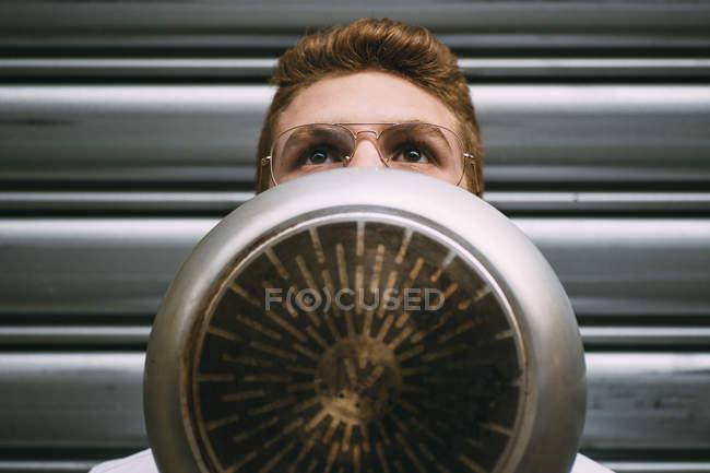 Homem jovem pensativo em copos cobrindo o rosto com frigideira e olhando para cima — Fotografia de Stock