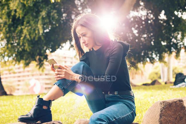 Giovane donna seduta sulla roccia e utilizzando smartphone nel parco — Foto stock
