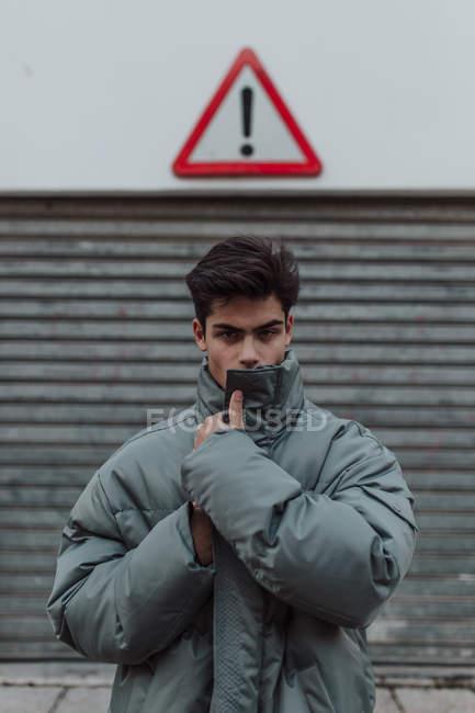 Portrait d'une adolescente en due forme veste grise chaude sous signe sur la rue — Photo de stock