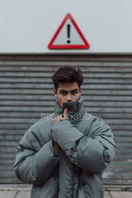 Portrait of Teenager in warm gray jacket standing under sign on street — Stock Photo