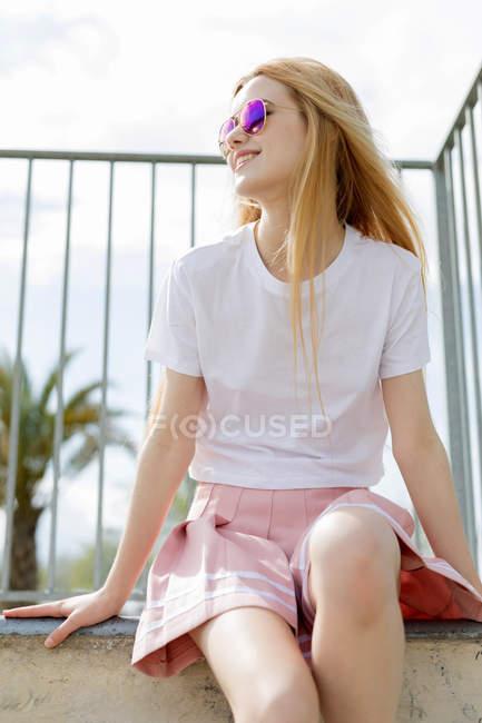 Улыбающаяся девочка-подросток в солнечных очках, сидящая на стене — стоковое фото