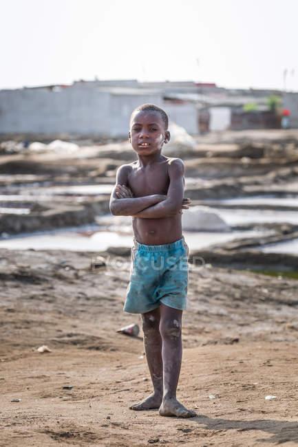 Angola - afrika - 5. april 2018 - kleiner afrikanischer Junge, der mit verschränkten Armen in die Kamera blickt — Stockfoto