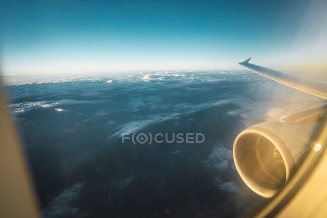 Shot through glass of plane glass with aircraft wing and turbine flying above blue cloudy sky — Stock Photo
