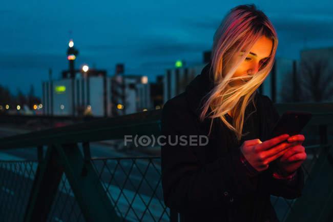 Femme blonde utilisant smartphone dans la rue au crépuscule — Photo de stock