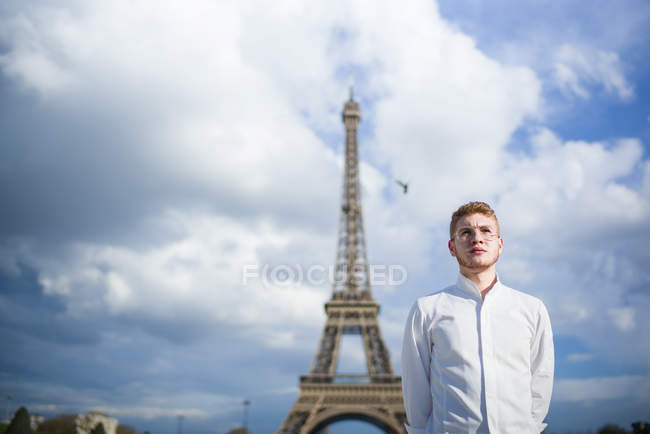 Confident Red-Hair cook in white shirt standing in front of Eiffel Tower in Paris — Stock Photo