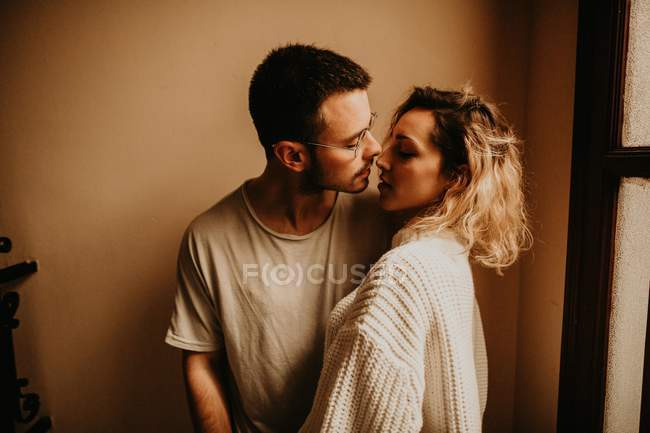 Affectionate couple embracing in front of wall at home — Stock Photo