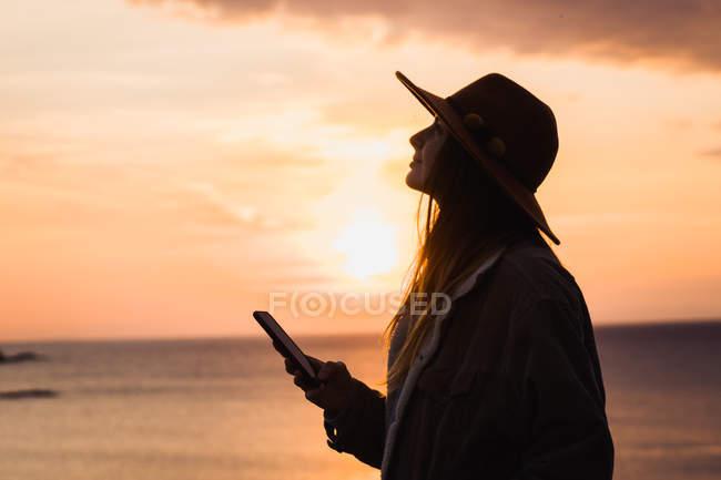 Жінка в капелюсі, проведення смартфон на березі моря, на заході сонця — стокове фото