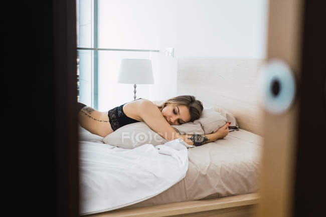 Sensual woman with tattoos wearing black lace underwear lying on bed — Stock Photo