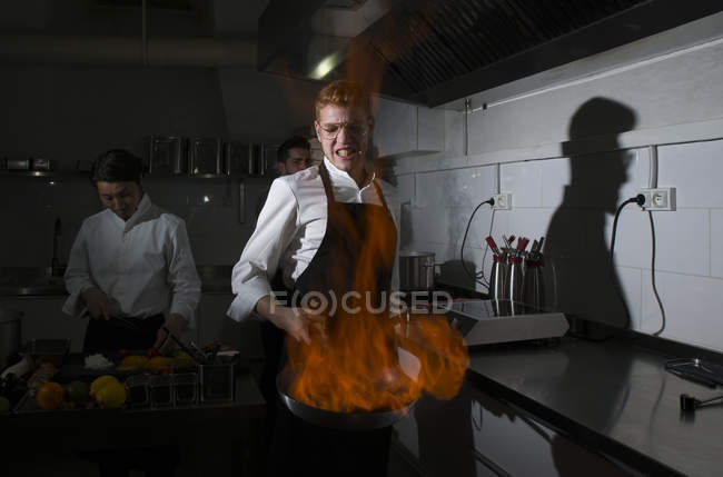 Cook making a flambe in restaurant kitchen with colleagues on background — Stock Photo