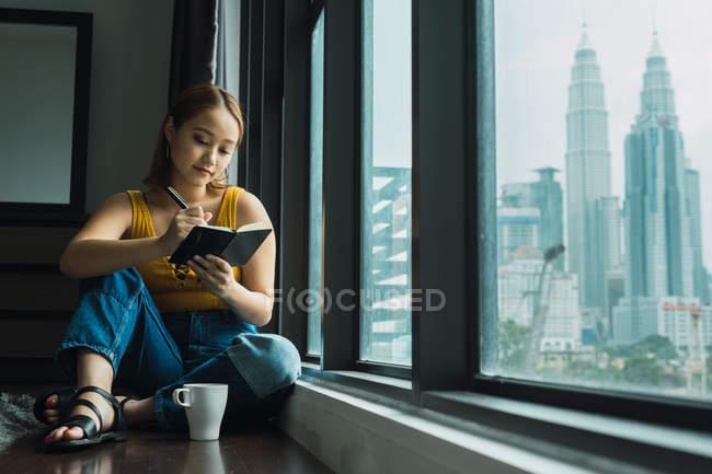 Femme avec coupe assis sur le plancher à la fenêtre et prendre des notes — Photo de stock