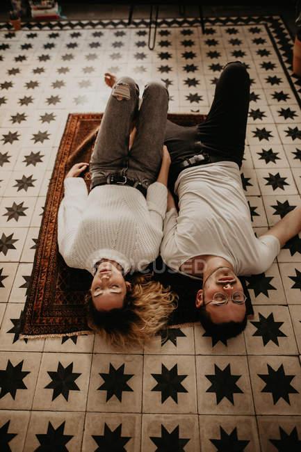 Jeune couple allongé sur le tapis avec les yeux fermés à la maison — Photo de stock