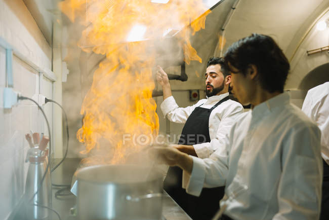 Cook making a flambe in restaurant kitchen with colleague watching — Stock Photo