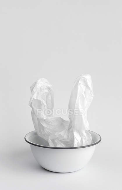 Crumpled white paper placed in metallic bowl on white background — Stock Photo