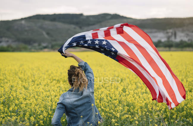 Woman holding american flag in field with yellow flowers on Independence Day — Stock Photo