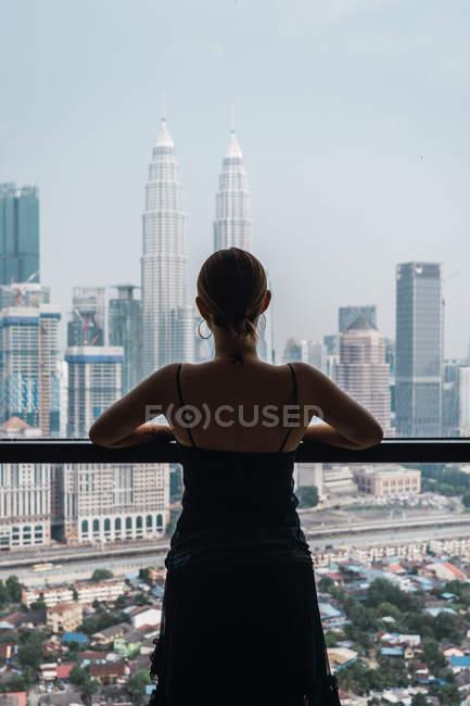 Mulher olhando para arranha-céus em pé na janela — Fotografia de Stock