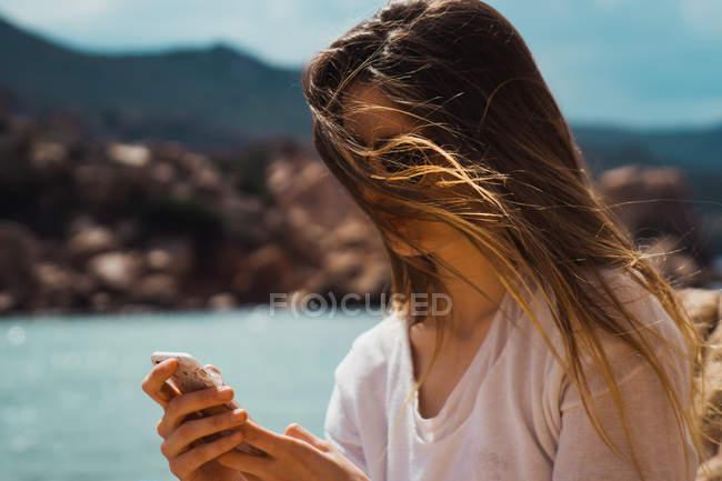 Mulher com cabelos castanhos compridos usando smartphone na beira-mar — Fotografia de Stock
