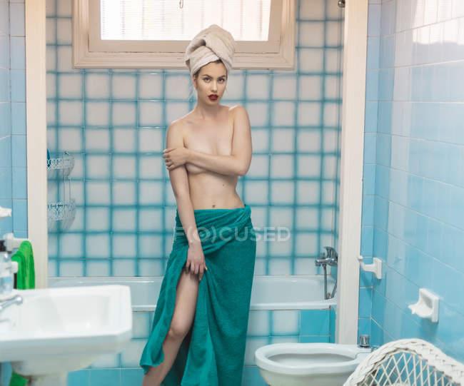 Jovem mulher topless envolvida em toalhas, olhando para a câmera no banheiro azul — Fotografia de Stock