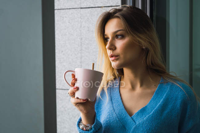 Pensive young woman drinking coffee at window — Stock Photo