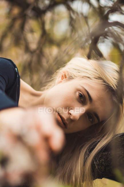 Giovane donna bionda appoggiata sull'albero e guardando la fotocamera — Foto stock