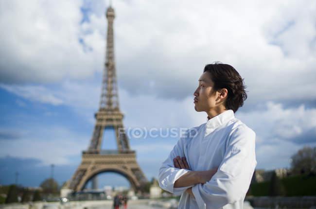 Японський шеф-кухар з обіймами перетнув стоячи перед Ейфелеву вежу в Парижі — стокове фото