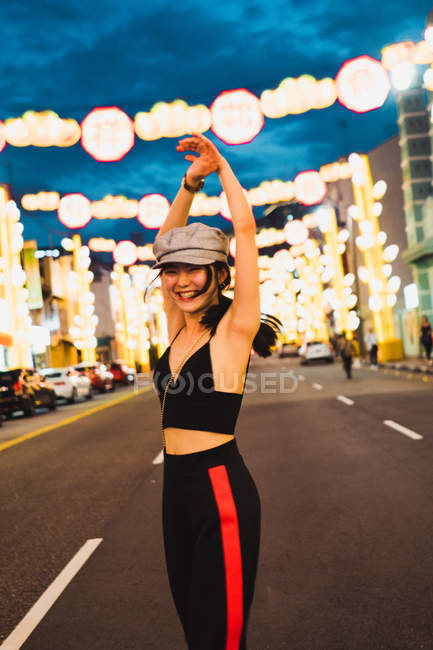 Fashionable young Asian woman walking with raised arms in illuminated city in evening — Stock Photo
